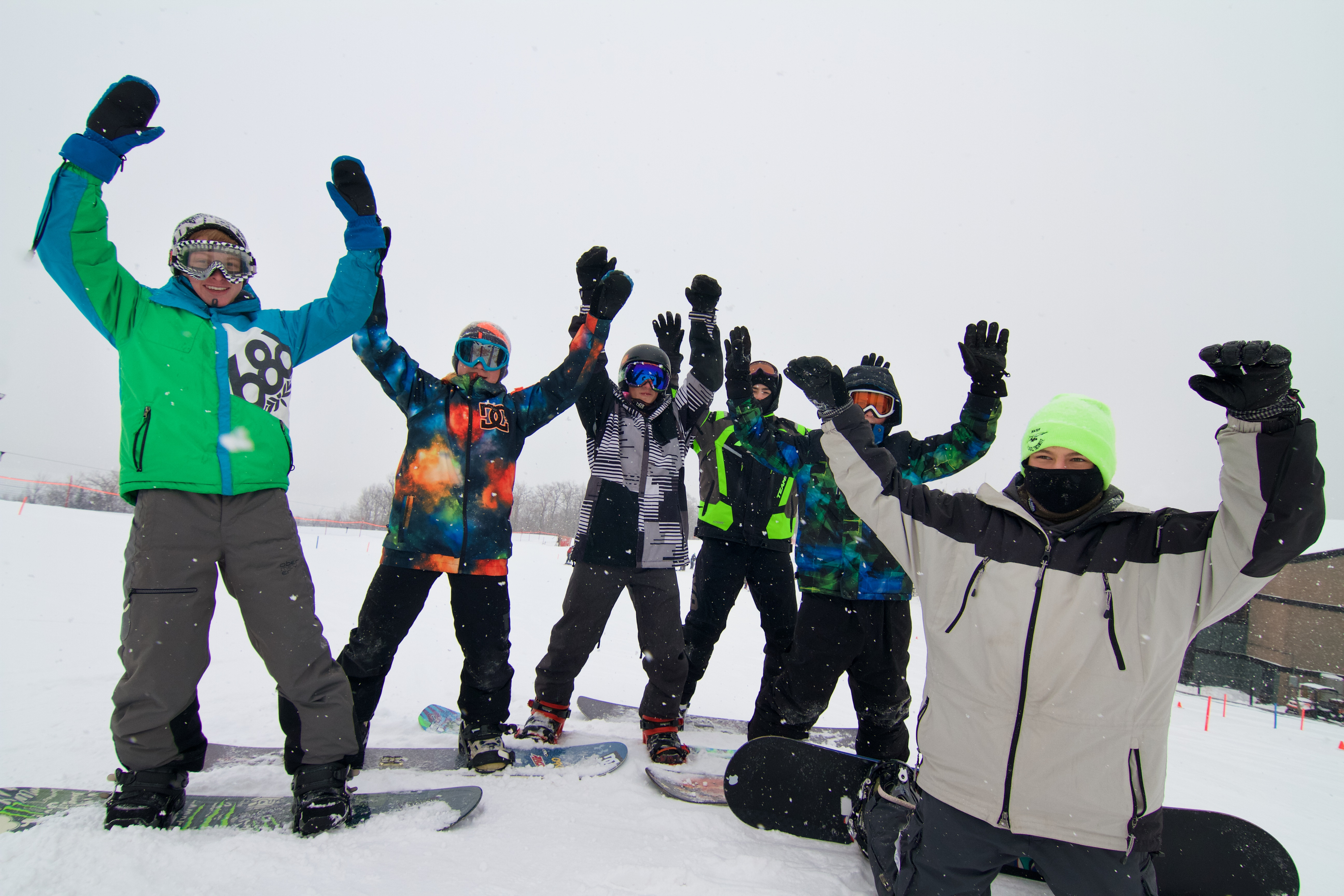6 boys on snowboards with their hands up