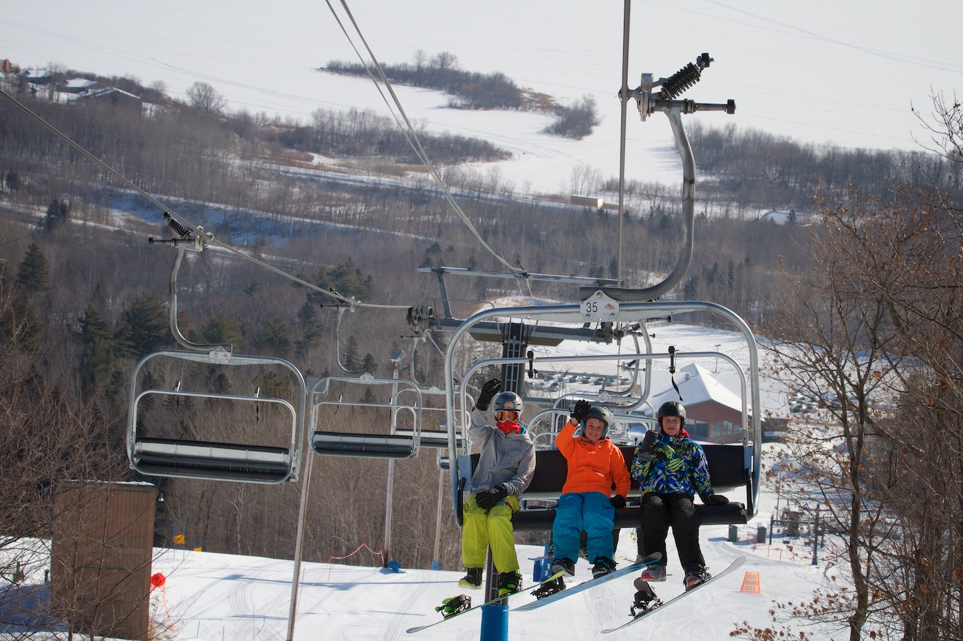 3 kids on a chair lift in the winter